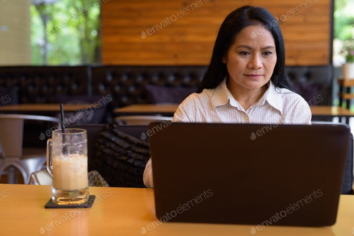 Mature Asian businesswoman relaxing at coffee shop