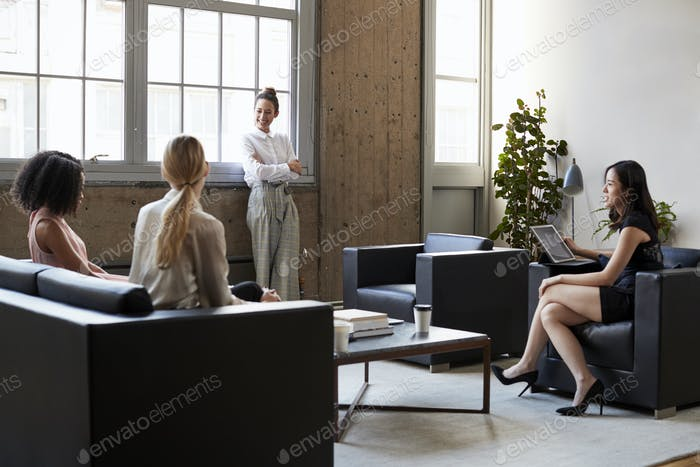 Standing female manager with arms crossed at casual meeting