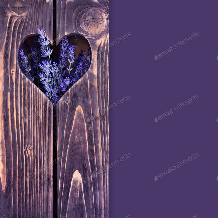 Wooden background with heart and flowers of lavender with space