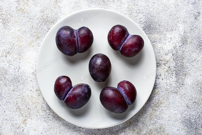 Ugly and normal plums. Abnormal organic fruit