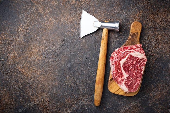 Roh marmoriertes Ribeye Steak und Metzgermesser