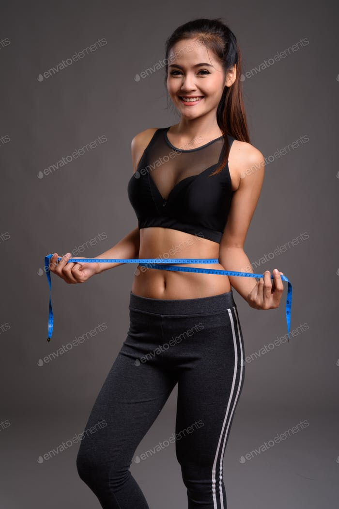 Young beautiful Asian fitness woman with slim waist holding measurement tape