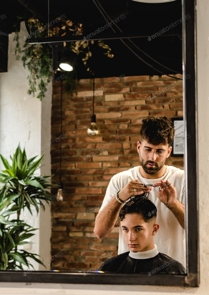 Confident teenager visiting hairstylist in barber shop