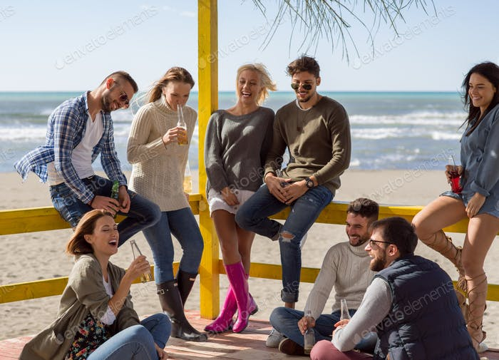 Group of friends having fun on autumn day at beach