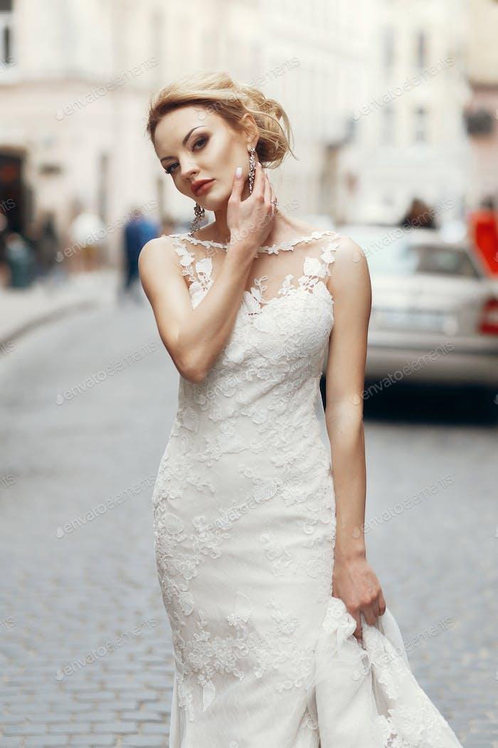 Stylish bride in white wedding dress with veil walking on street