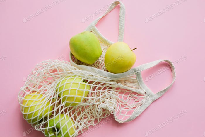 Apples in reusable tote bag on pink background flat lay