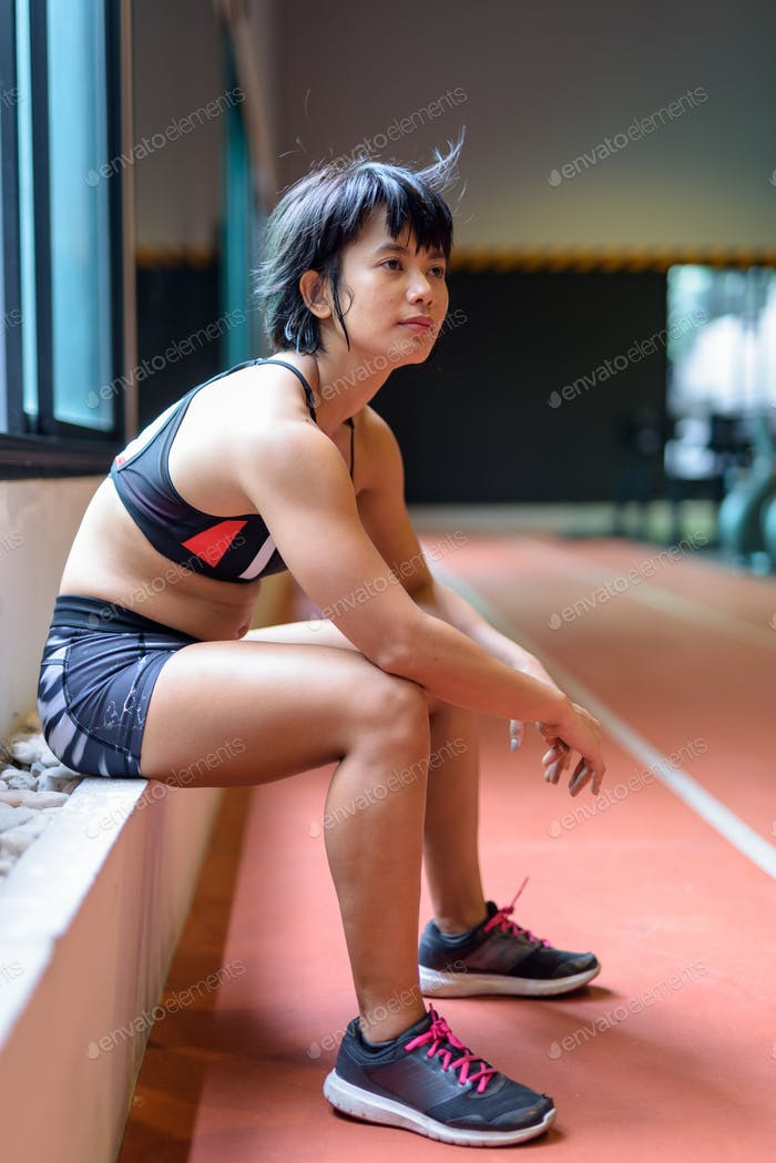 Young beautiful Asian woman sitting and relaxing at the gym