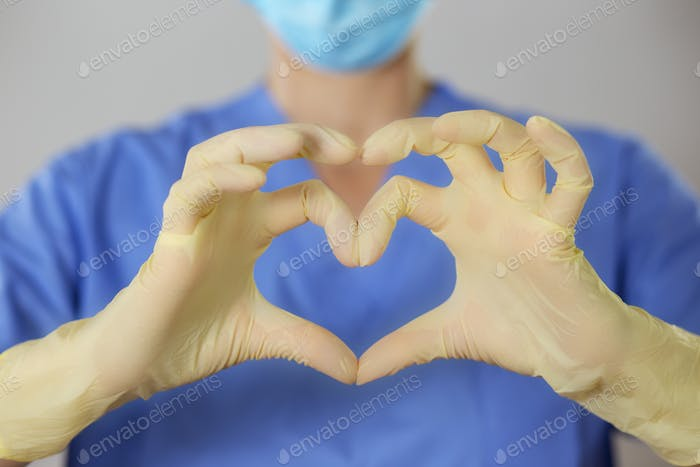 Hands in rubber gloves making the heart symbol in front of a healthcare professional in uniform