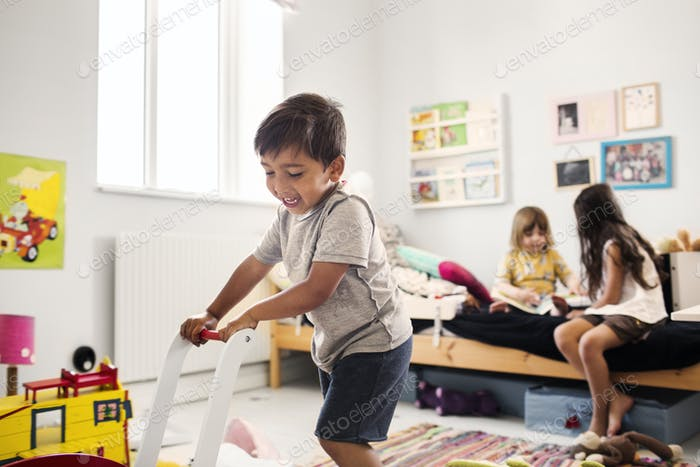 Children (2-3, 6-7) playing in domestic room