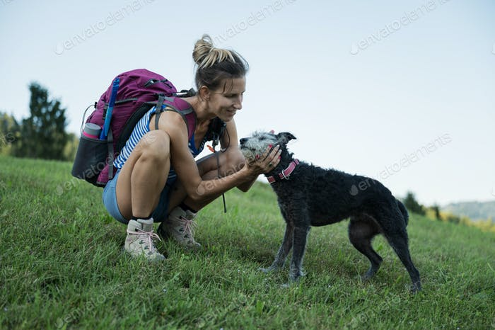Woman patting her dog on a hike