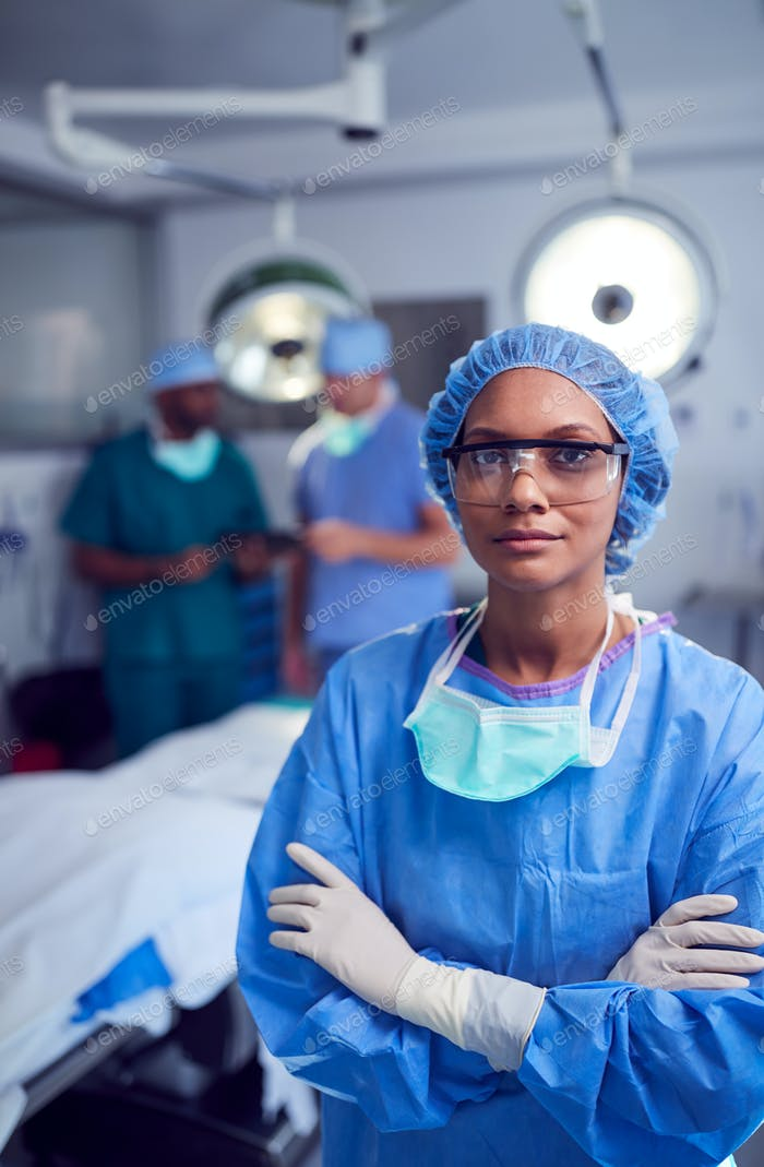 Portrait Of Female Surgeon Wearing Scrubs And Protective Glasses In Hospital Operating Theater