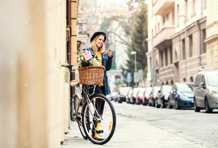 Junge Frau mit Fahrrad und Smartphone in sonniger Frühlingsstadt.