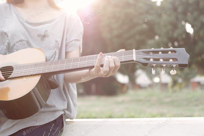 Geschnittene Ansicht Frau spielt Gitarre an einem sonnigen Tag
