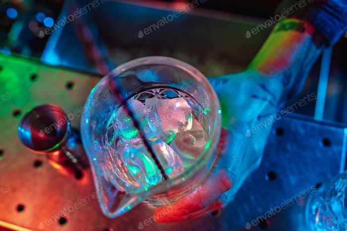 Top view of barman finishes preparation of alcoholic liquor and ice cocktail in multicolored neon