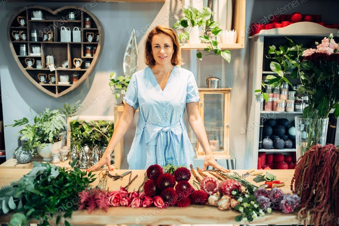 Florist at the table with flowers in floral shop