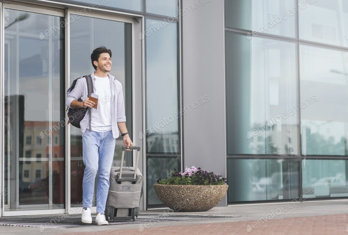 Happy guy going out of airport building with luggage