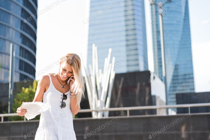 Happy blonde woman walking is hot and is using a fan and a mobile phone