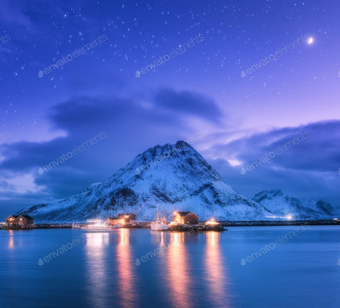 Fishing boats near pier on the sea and snowy mountains at night