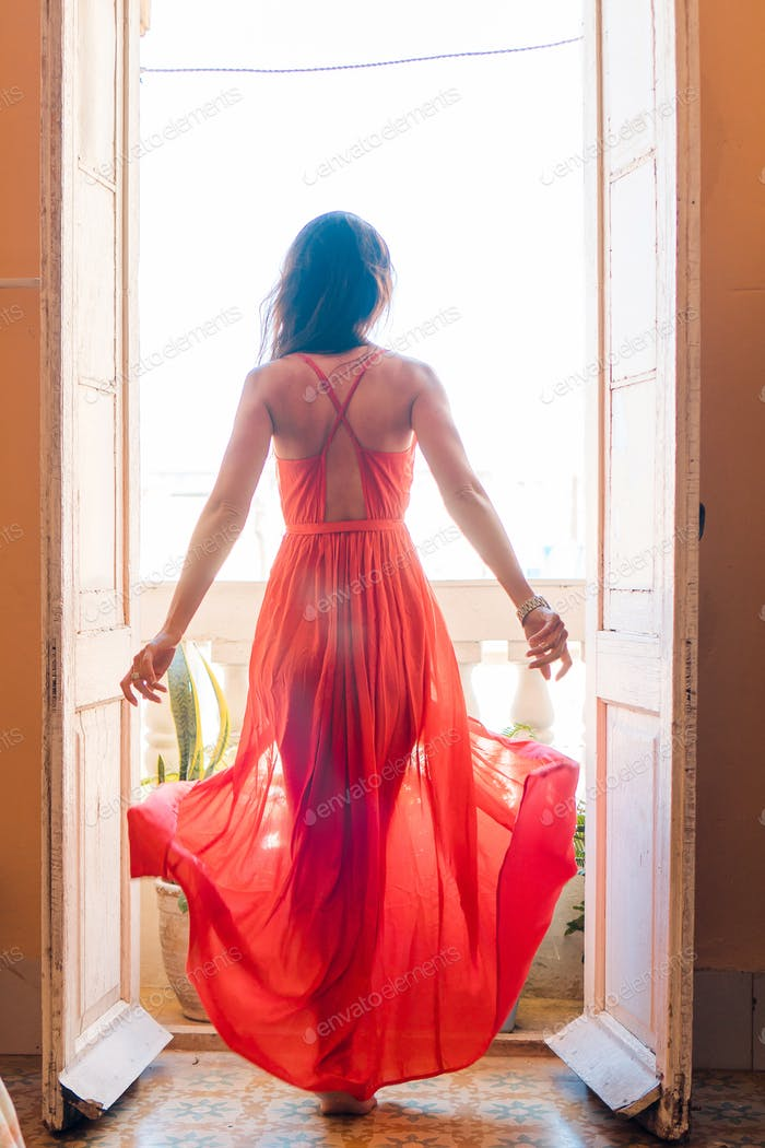Young beautiful woman in red dress on old balcony in apartment in Old Havana, Cuba
