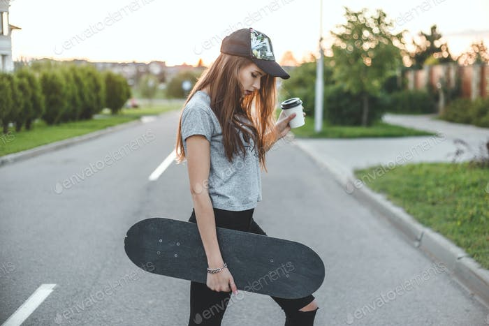 skater girl with coffee cup in front of the sun starts her day.