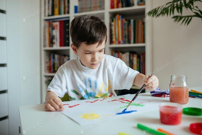 Left handed cute preschooler boy painting picture.