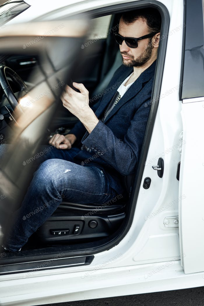 An adult businessman is sitting in his new car and browsing some news