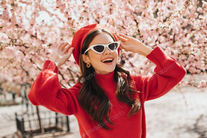 Woman in glasses and red beret enjoys blossoming of sakura. Lady in cashemere sweater smiling. Port