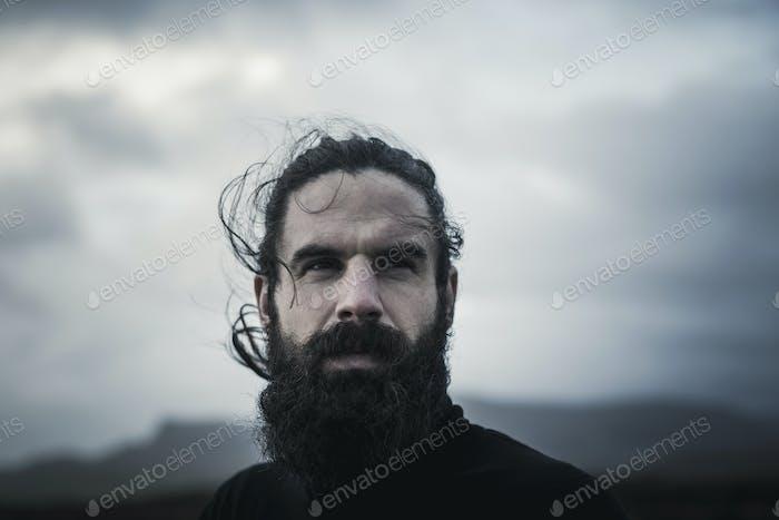 Мужчина с черными волосами, полной бородой и усами.