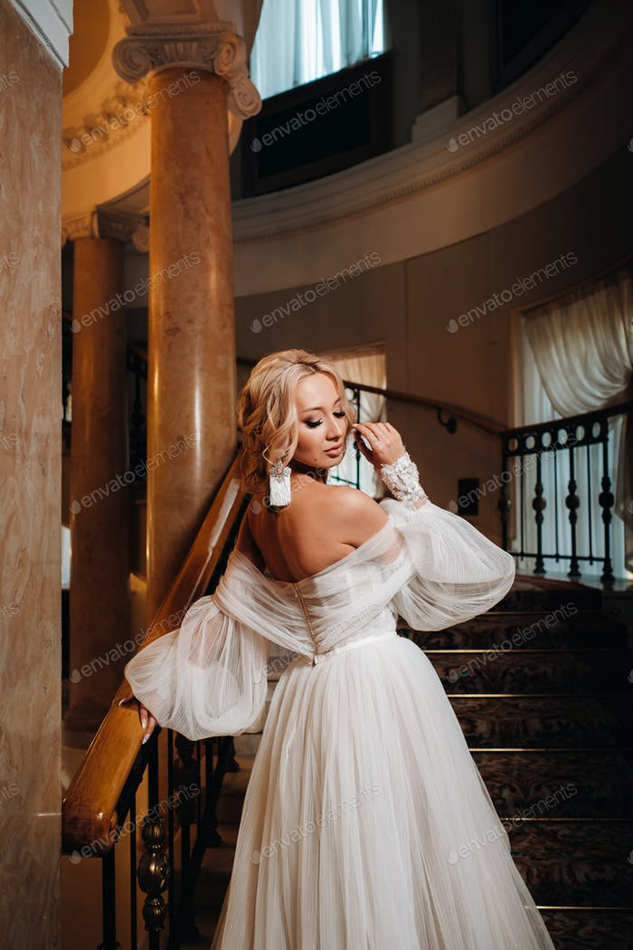 Portrait of a beautiful bride climbing a beautiful staircase
