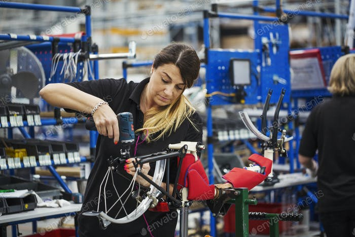 Female skilled factory worker assembling a bicycle in a factory working on the frame and wheels.