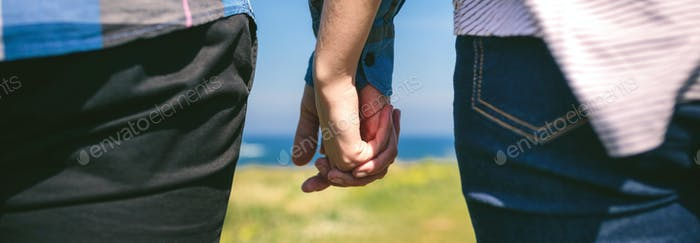 Unrecognizable couple holding hands
