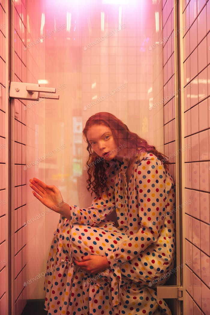 Young redhead curly woman in cafe at latrine at shower