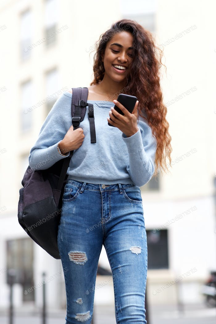 young woman walking with mobile phone and bag in city