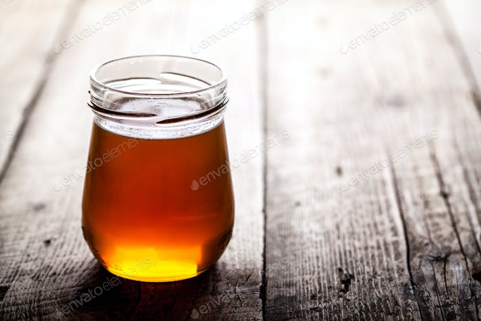 Bowl of honey on wooden table. Symbol of healthy living and natural medicine. Aromatic and tasty.