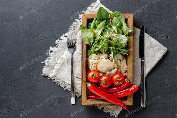 Cooking ingredients in wooden box on dark background, top view, copy space