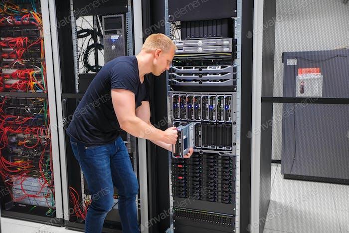 Computer Engineer Installing Server Into Blade Enclosure
