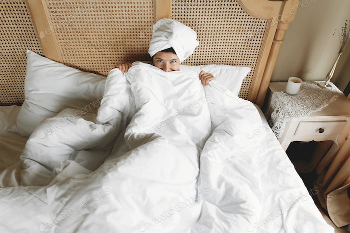 Beautiful happy young woman hiding under white sheets, lying on bed in hotel room