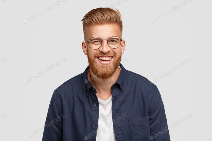 Pleased cheerful redhaired male with pleasant smile, giggles joyfully, spends free time with girlfri