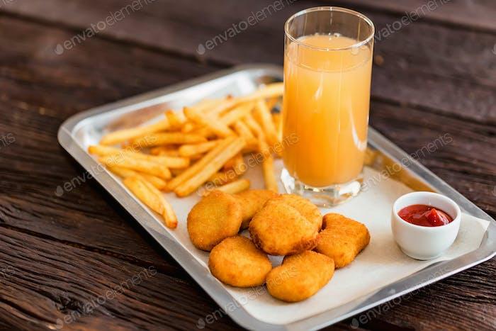 Close up Huhn Nuggets und Pommes mit Sauce und Saft auf Teller
