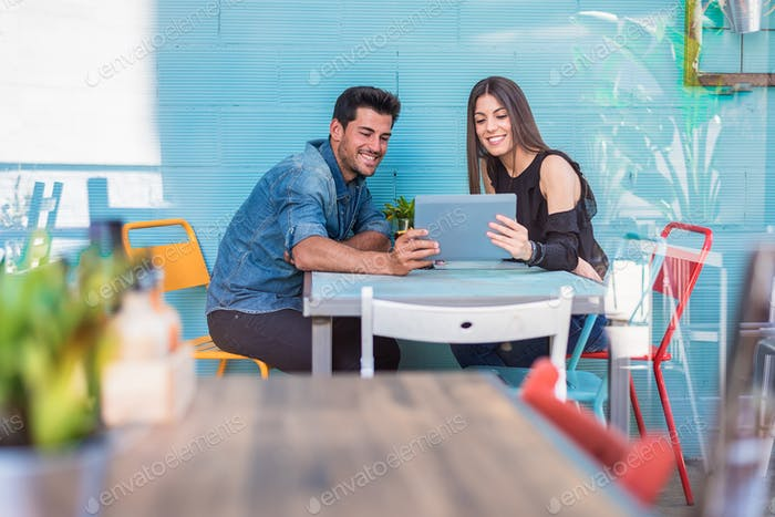 Happy young couple seating in a restaurant with a tablet