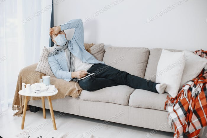 Sick man sitting on sofa at home