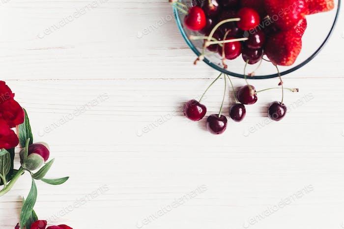 fresh cherries and strawberries in stylish glass bowl