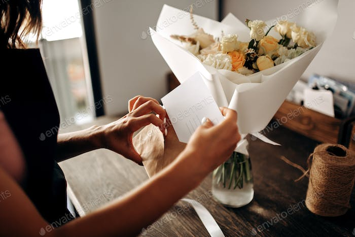 Bouquet of flowers in pastel colors packed in white paper is in a vase. Florist puts a postcard in