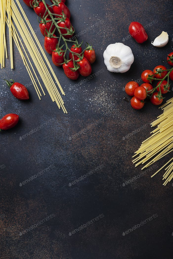 spaghetti, tomato and garlic on the black table