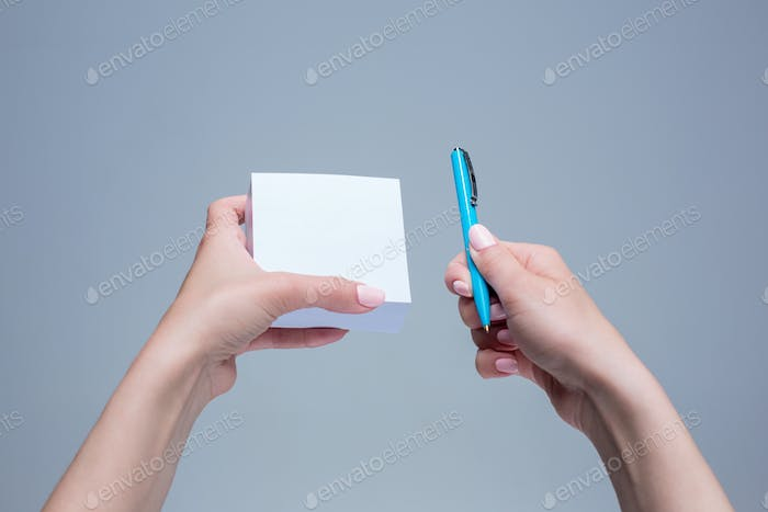 The notepad and pen in female hands