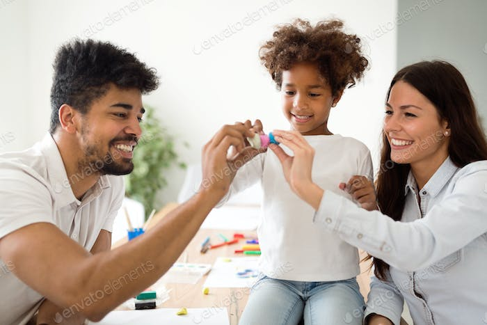 Family lifestyle portrait of a mum and dad with their kid
