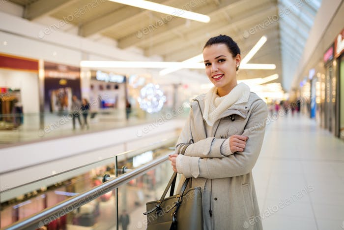 Happy young woman posing in shopping mall
