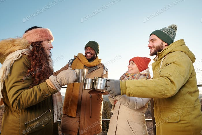 Happy young friends in winterwear cheering up with hot tea and chatting