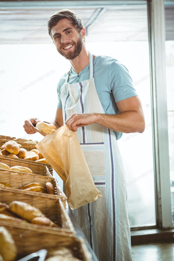 Smiling waiter taking bread with tongs at the bakery