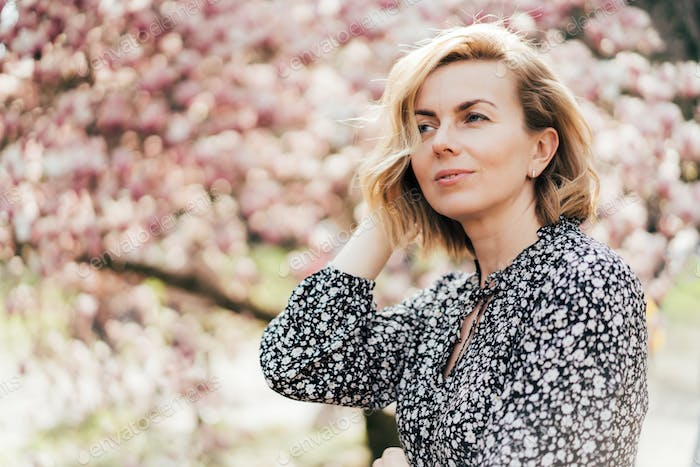 Beautiful woman in her forties. Profile portrait with a pink flowering magnolia tree as background.